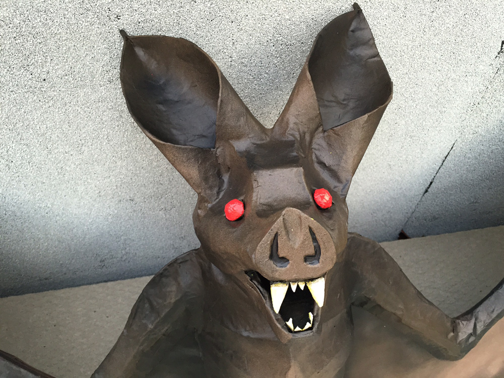 Papier maché bat -- painting the eyes and teeth