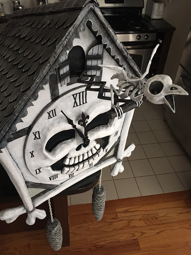 Cuckoo clock skull mask with bird skeleton