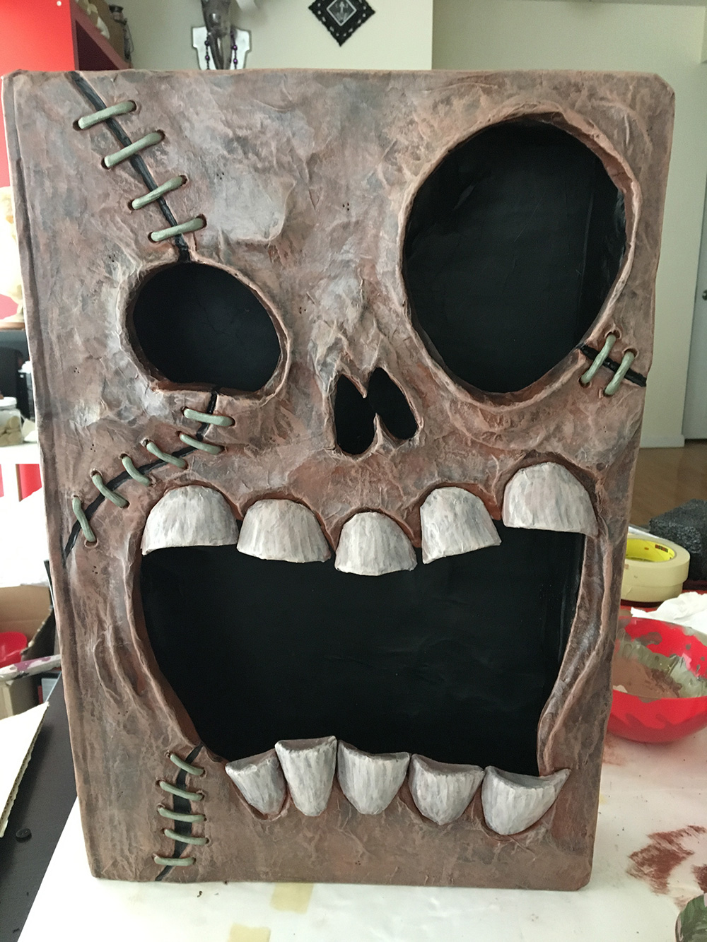Haunted book sculpture - painting the details with acrylic paint