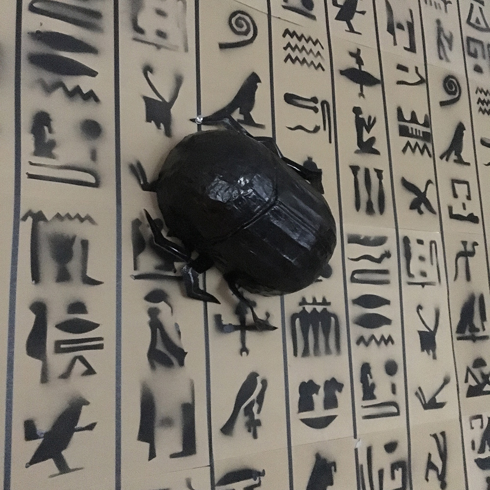 Paper mache scarab decorations - displayed on a wall of hieroglyphs