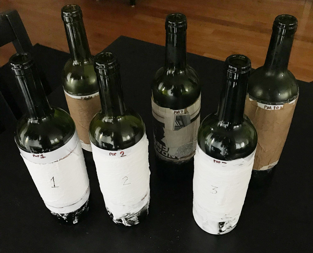 Paper mache and plaster cloth experiment on wine bottles