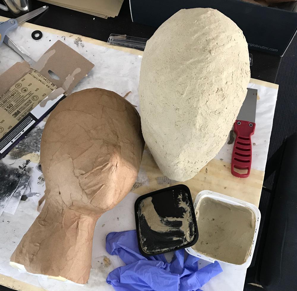 Applying wood filler in between layers of paper mache