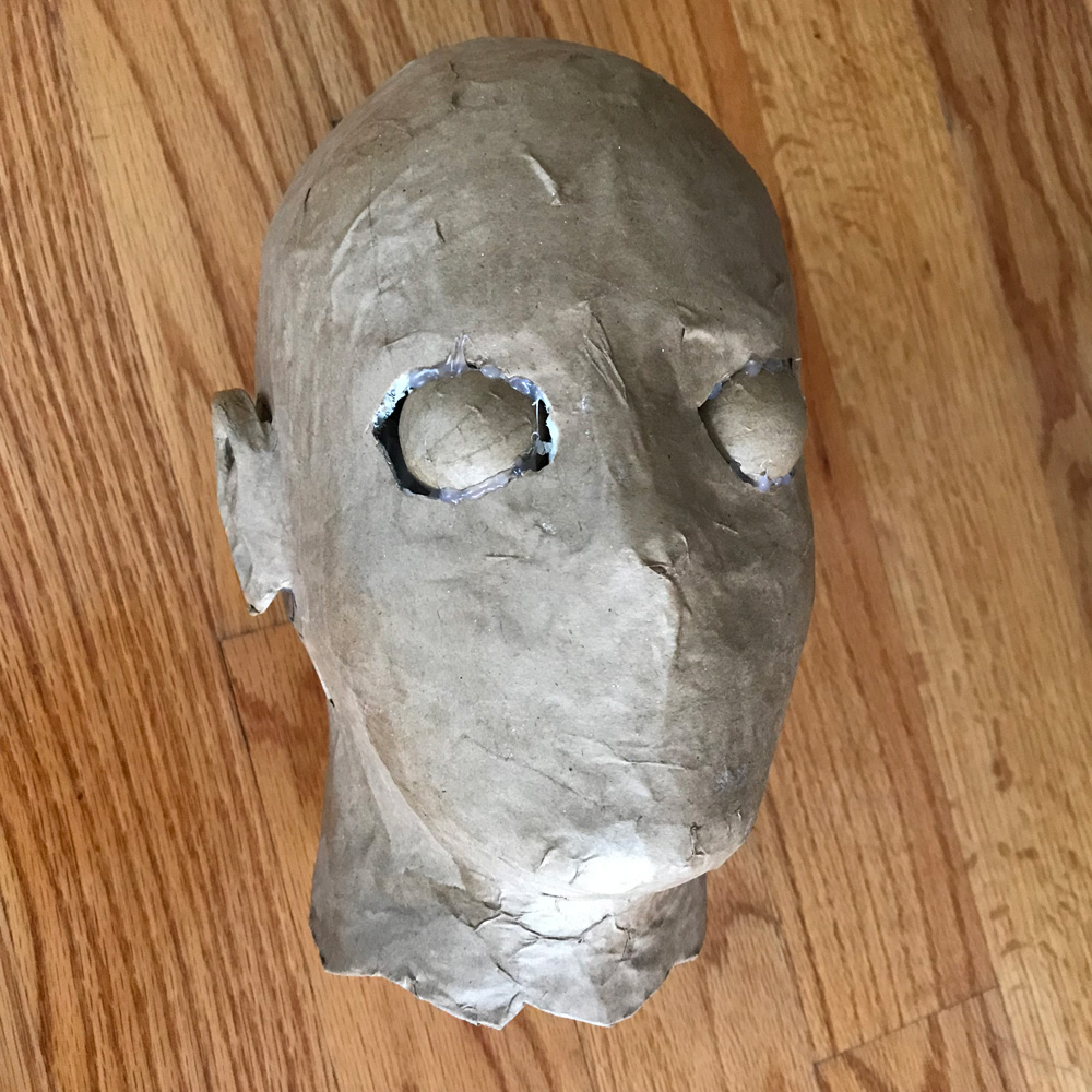 paper mache heads -- gluing eyeballs in place