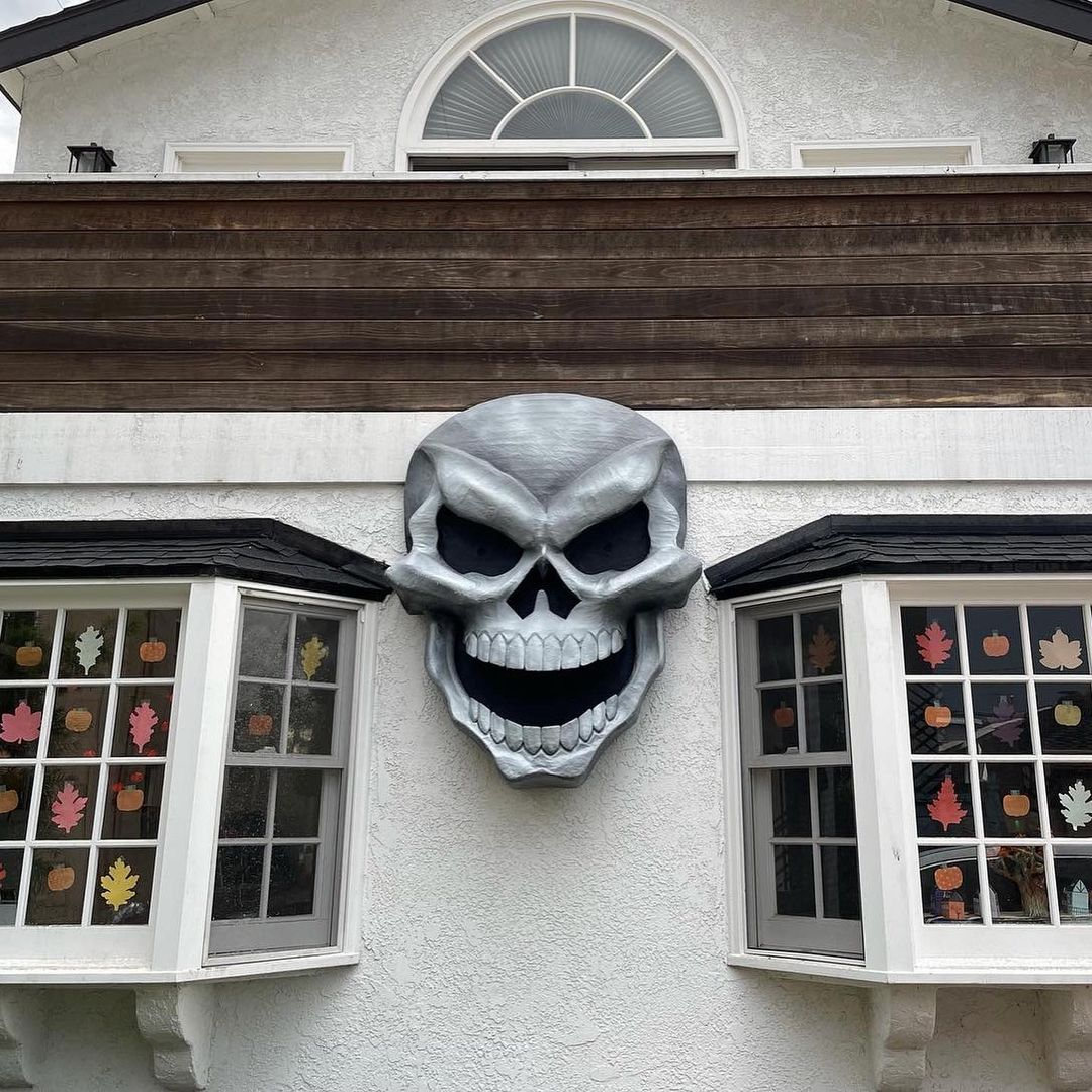 Giant paper maché skull Halloween decoration - hanging on house